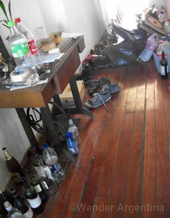 bottles of beer and trash in a messy student apartment