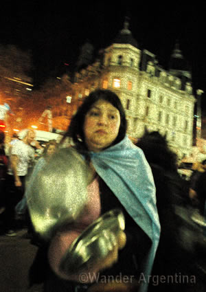 a woman banging a pot in a protest in Buenos Aires