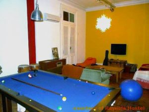 A common room with a pool table, instruments and a TV at Rayuela Hostel in Buenos Aires