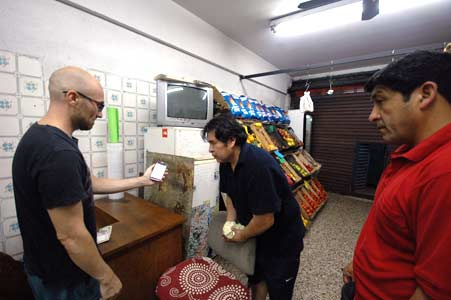 Ryan Drift, an American bitcoin enthusiast shows friends how to make a bitcoin transaction in a Buenos Aires vegetable shop